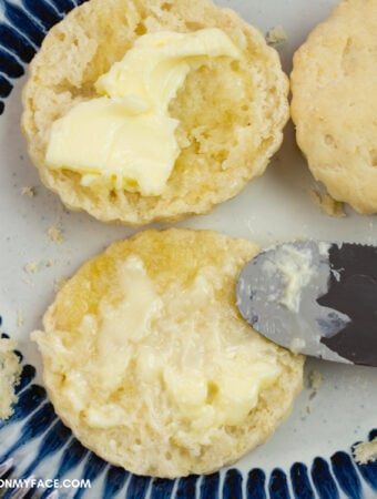 homemade biscuits cut open with butter spread on