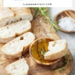 Homemade Italian Bread recipe; a sliced loaf of homemade Italian bread on a wooden serving platter.