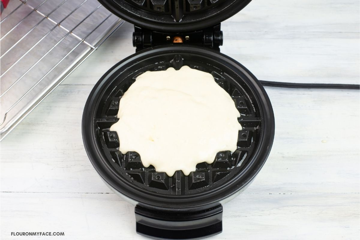Filling a waffle iron with batter.