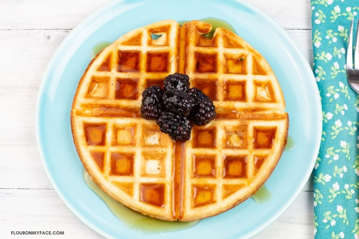 A serving of waffles on a plate topped with berries and syrup.