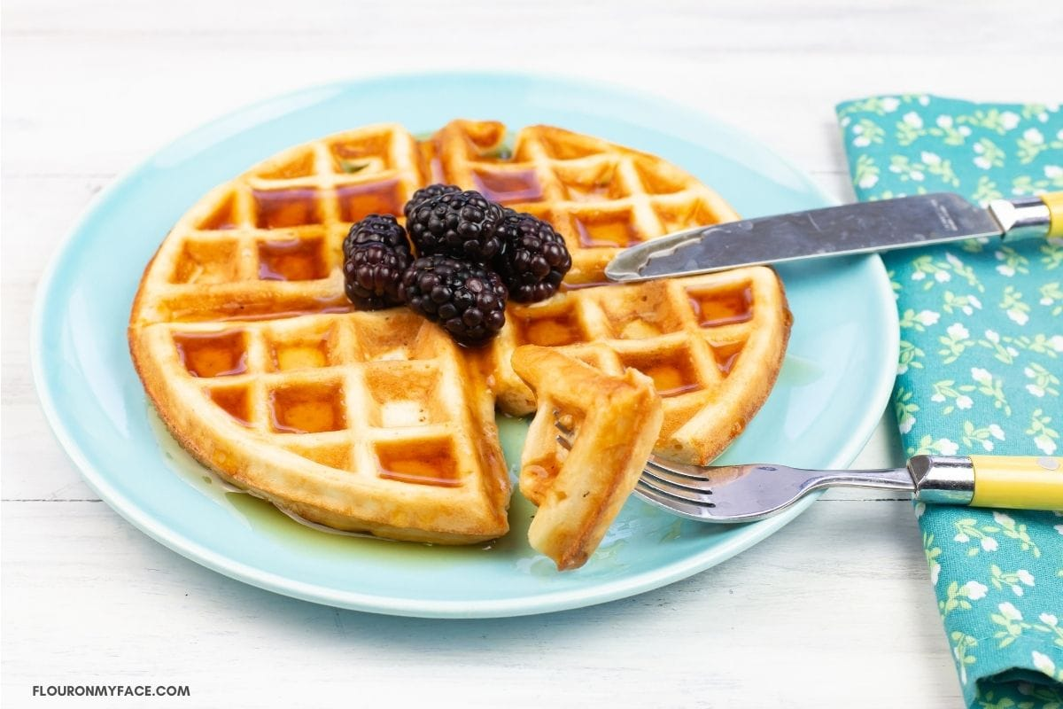 Sourdough waffles topped with blackberries on a plate.