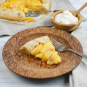 A slice of Rustic Peach Pie on a brown plate with the cut pie in the background.