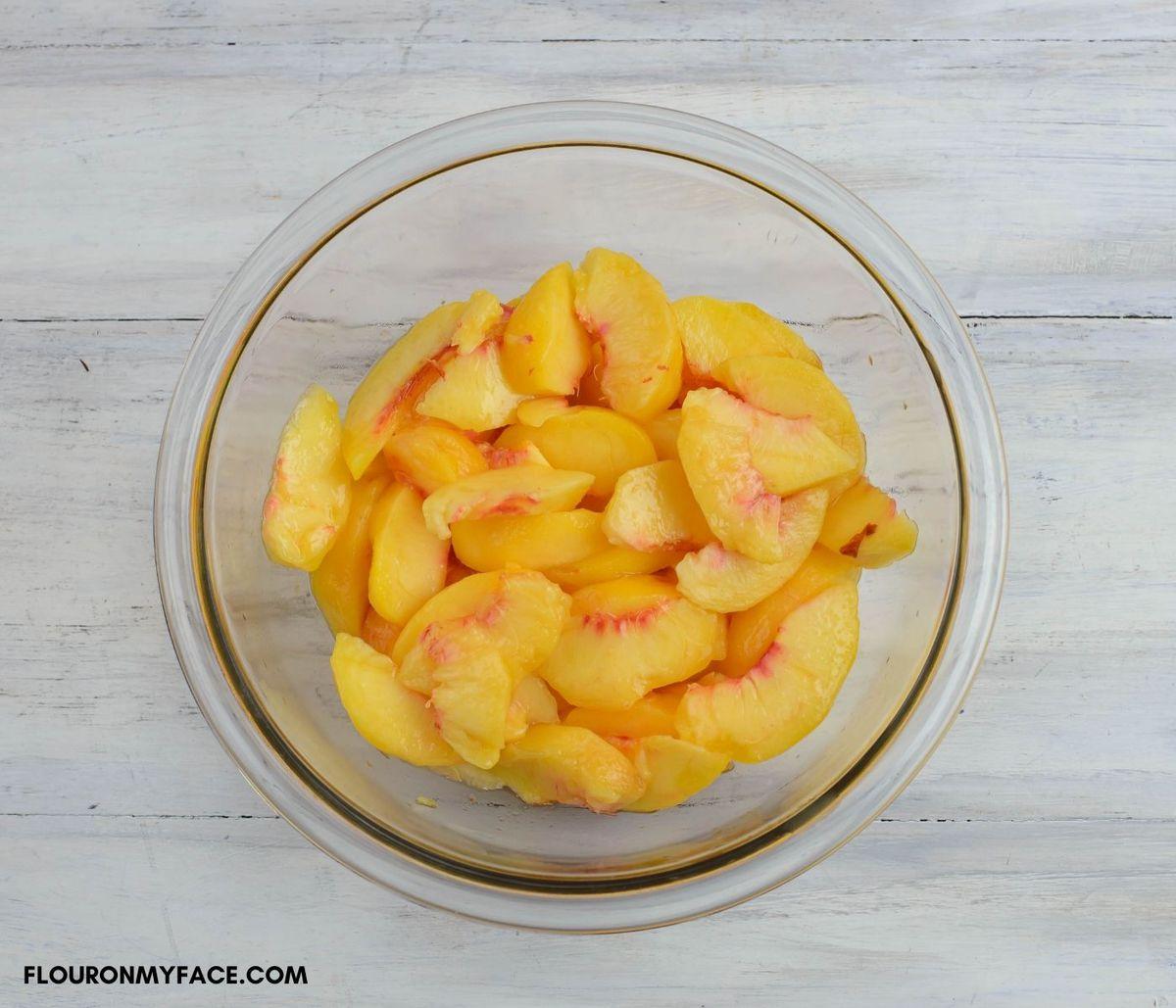 Fresh peaches sliced in a glass bowl.