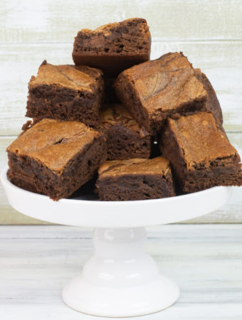 Freshly baked Nutella Brownies on a white glass cake stand