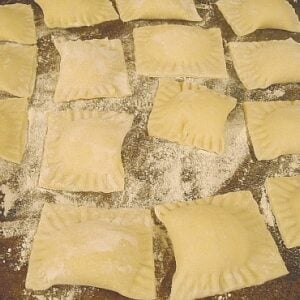 homemade ravioli covered with flour on a cookie sheet