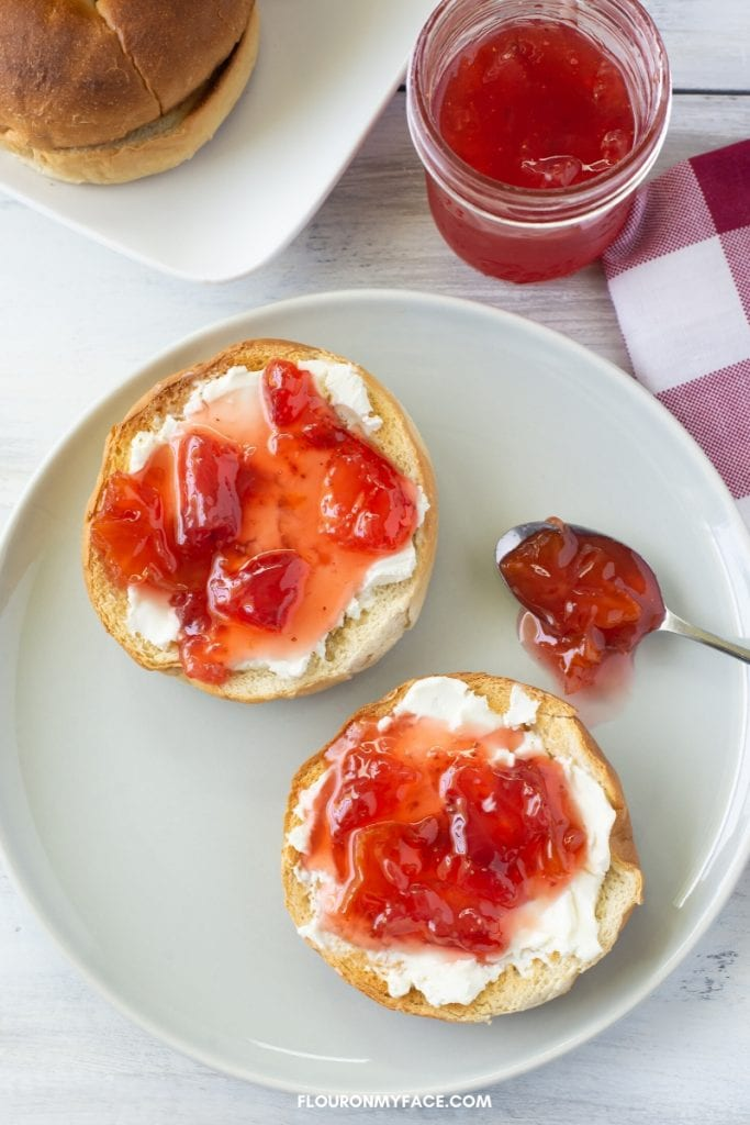 Carambola Strawberry Jam on a bagel with a spoon on a plate