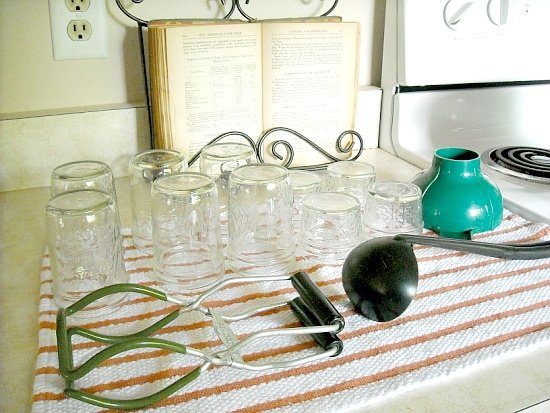 Preparing canning equipment before you start canning. Sterilized jars and equipment on the counter on a clean dish towel