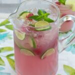 A glass pitcher filled with pink lemonade with berries, lime slices and ice cubes floating.