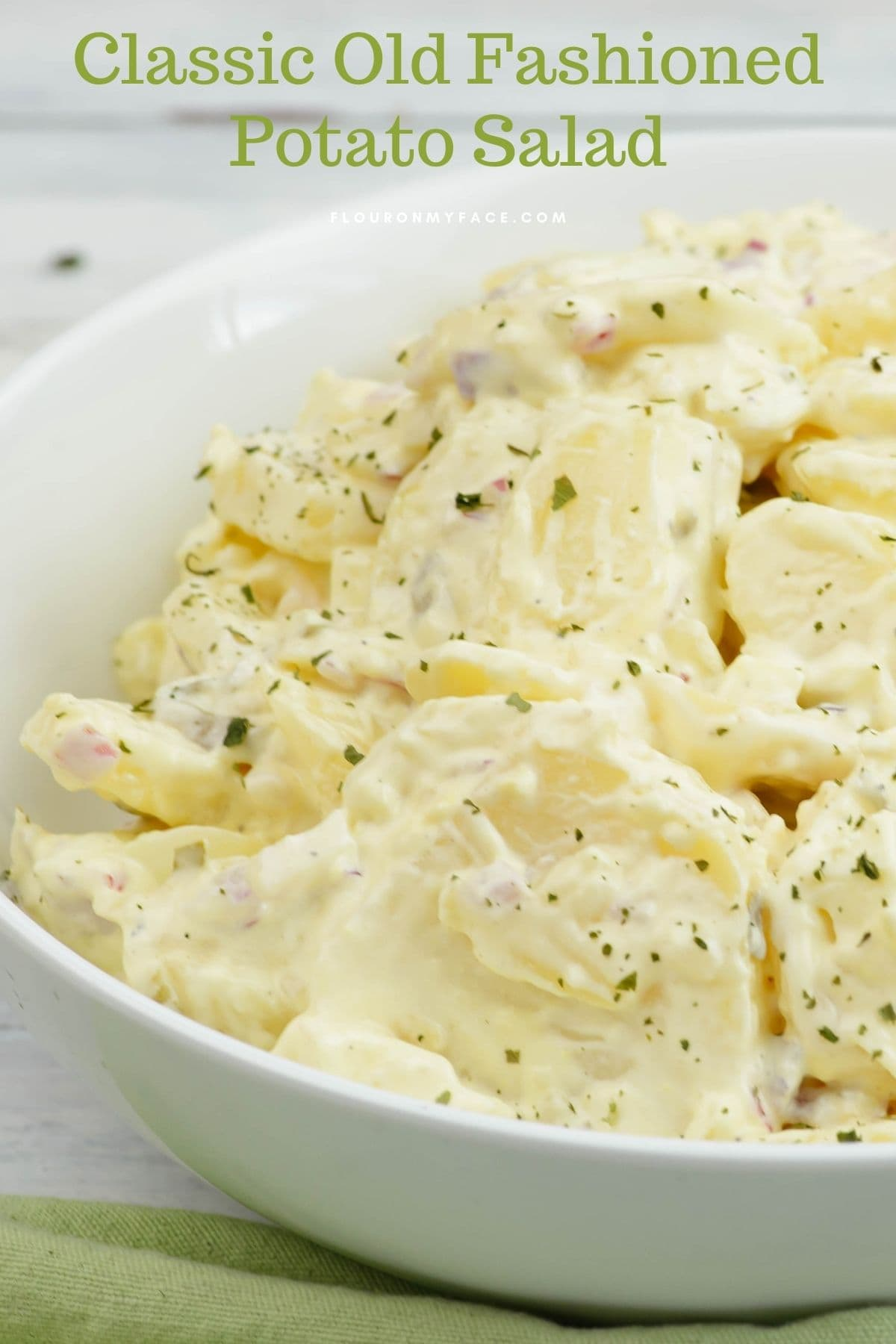A vertical image of a bowl of old fashioned potato salad.