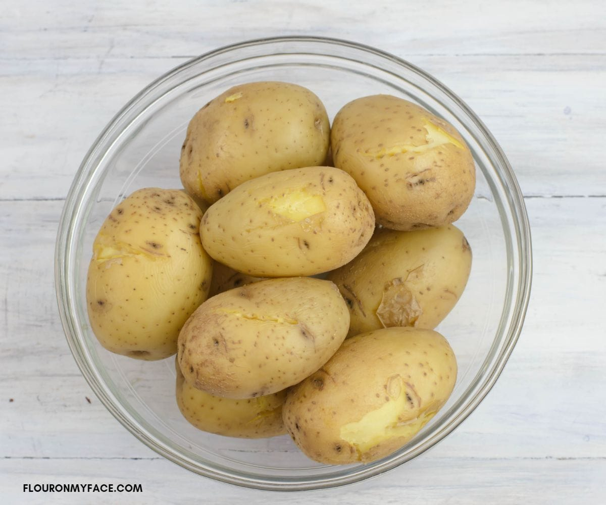 A glass bowl filled with unpeeled cooked yellow potatoes.