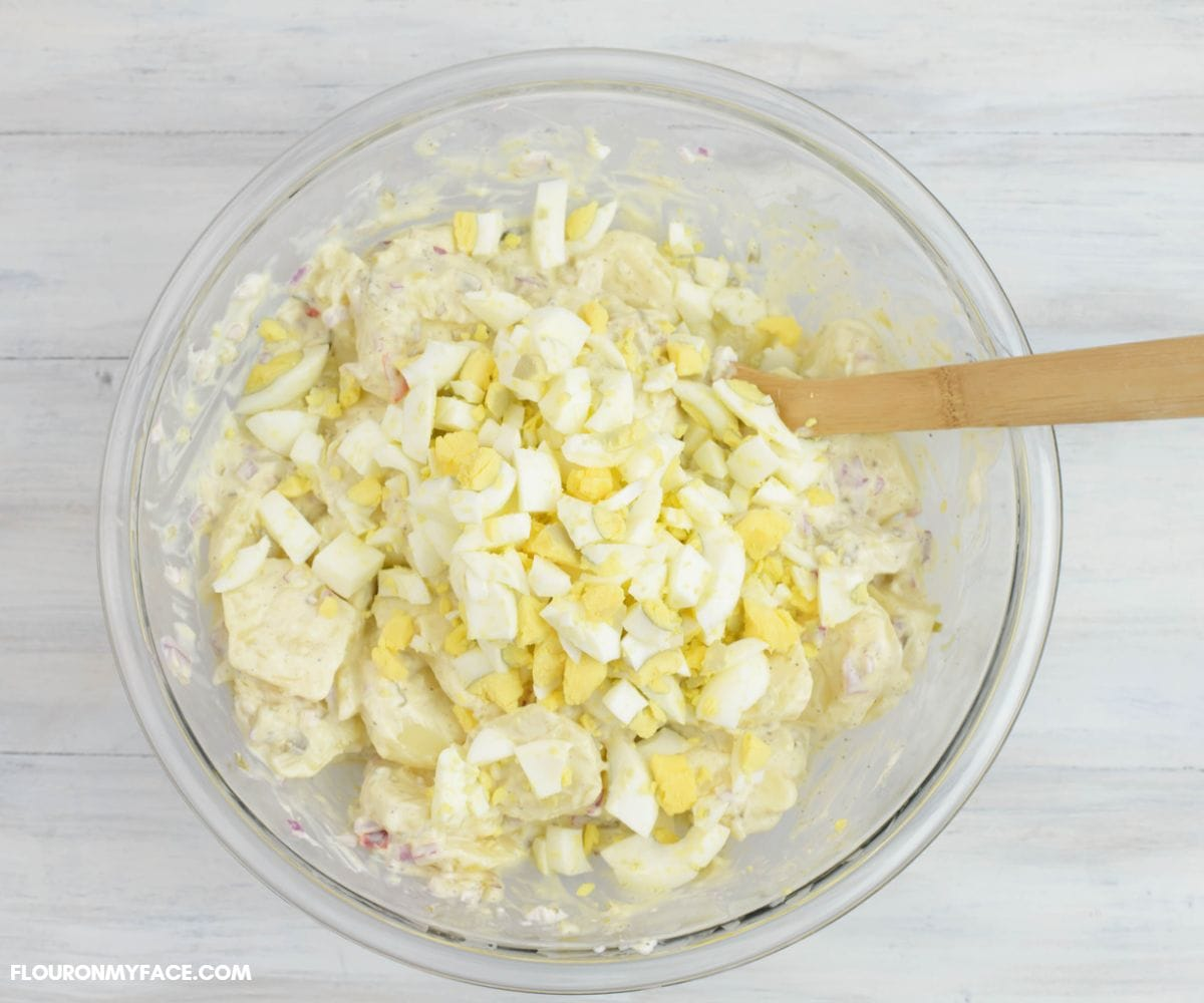 Mixing egg potato salad in a large bowl.