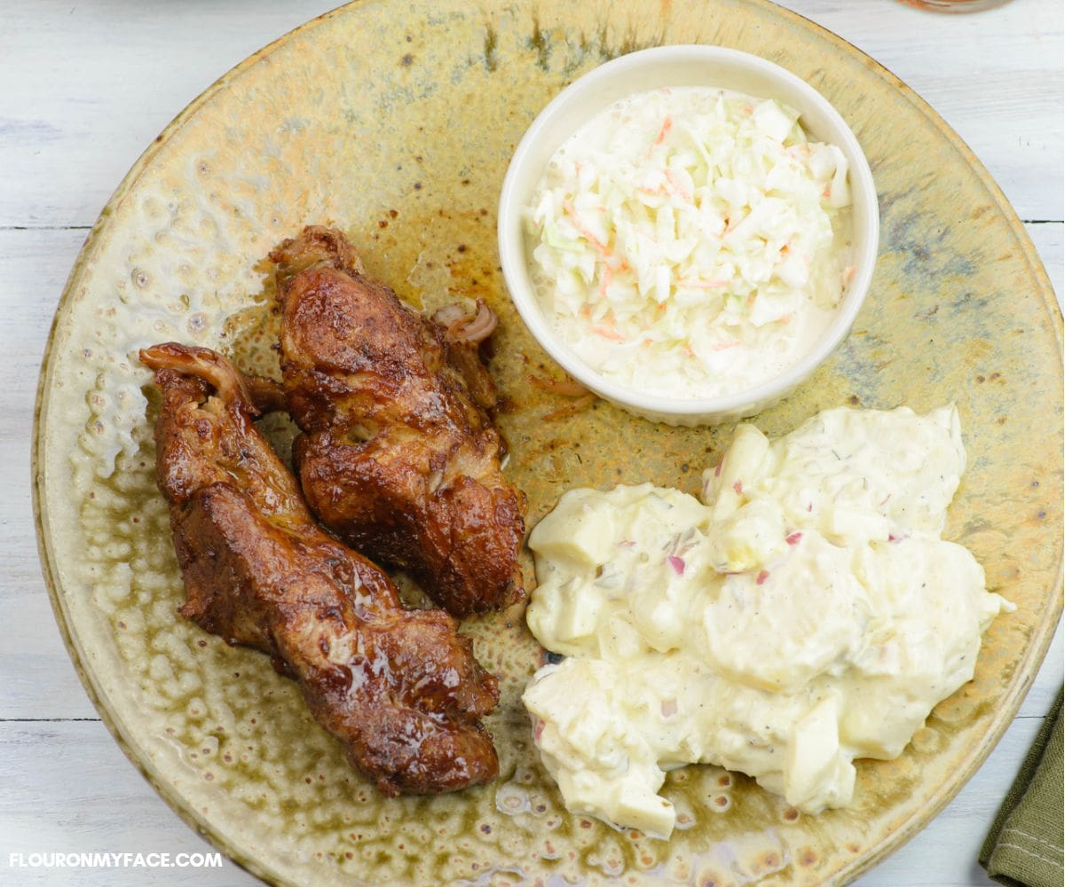 Homemade potato salad and Cole slaw served with bbq ribs on a dinner plate.