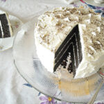 Vegan Triple Layer Chocolate Cake recipe on a vintage glass cake plate with a slice cut and on a cake plate.