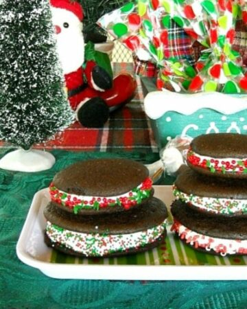 A decorative plate with a stack of chocolate peppermint whoopie pies.