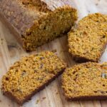 Sliced carrot cake bread on a wooden cutting board.