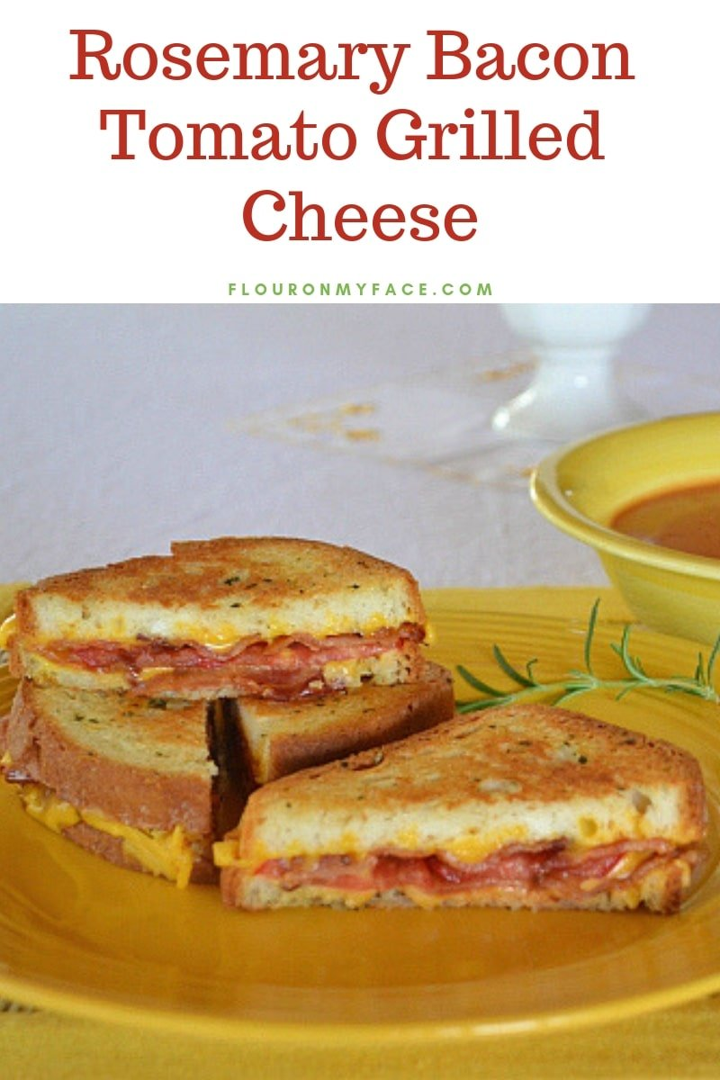 Rosemary Bacon Tomato Grilled Cheese Sandwich stacked on a yellow plate served with tomato soup