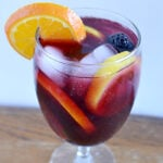 a wine glass filled with Sangria and fruit