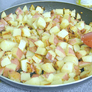 Frying cubed potatoes in a skillet.