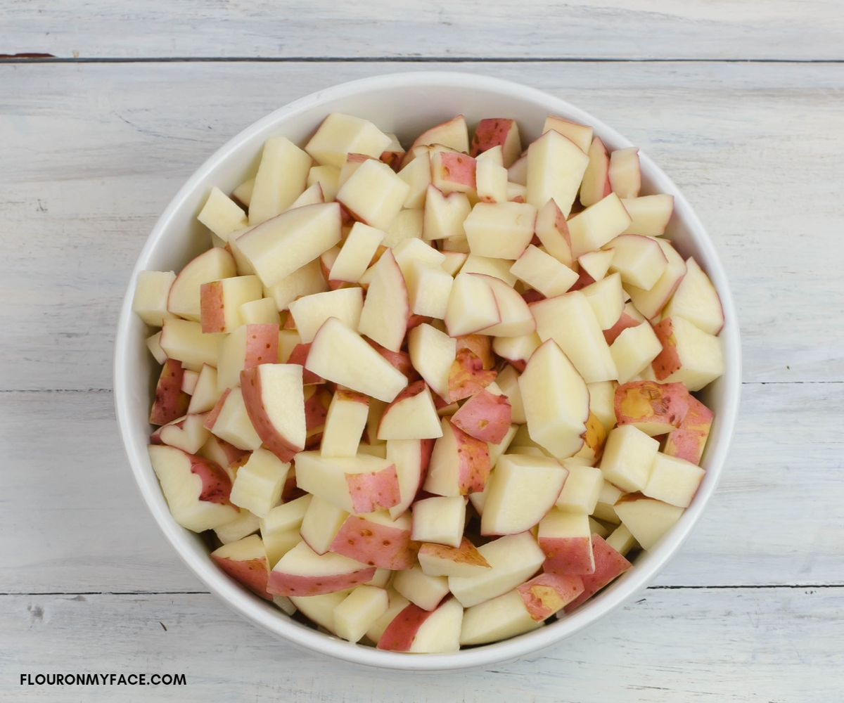 Cubed red potatoes in a large white glass bowl.