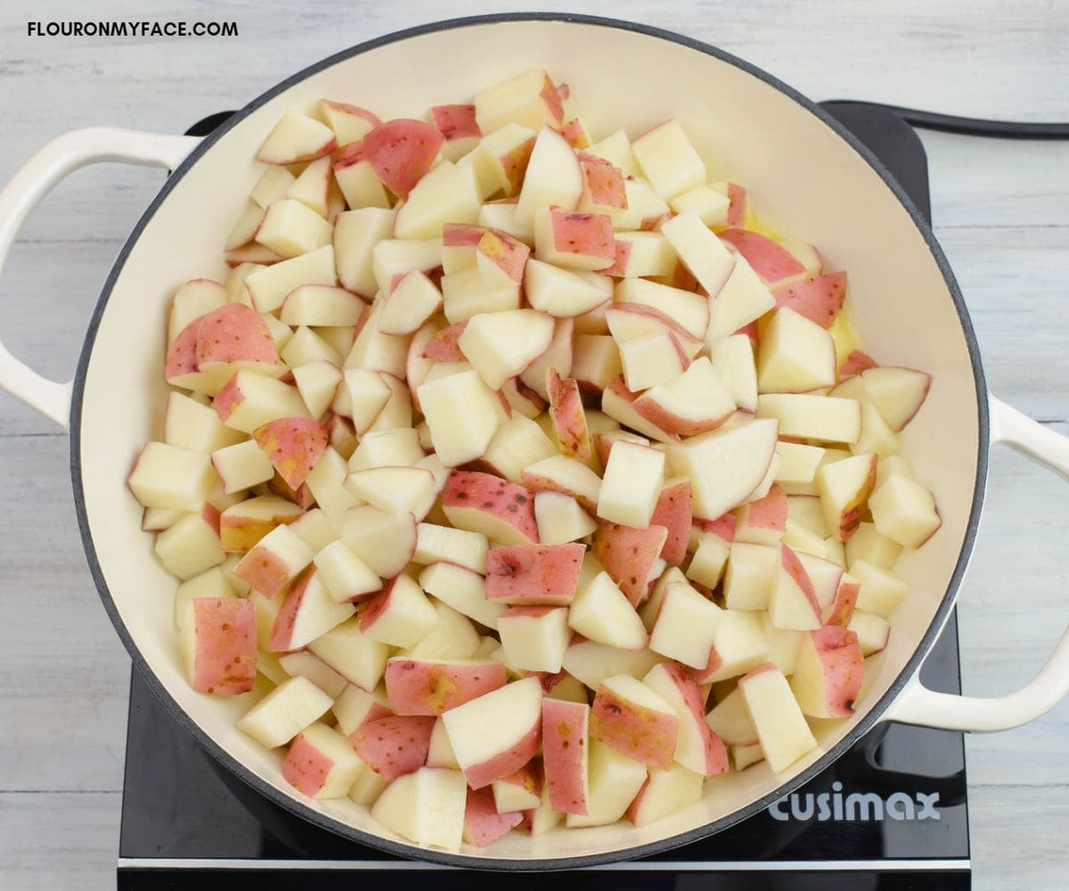 Adding cubed red potatoes to a hot skillet.