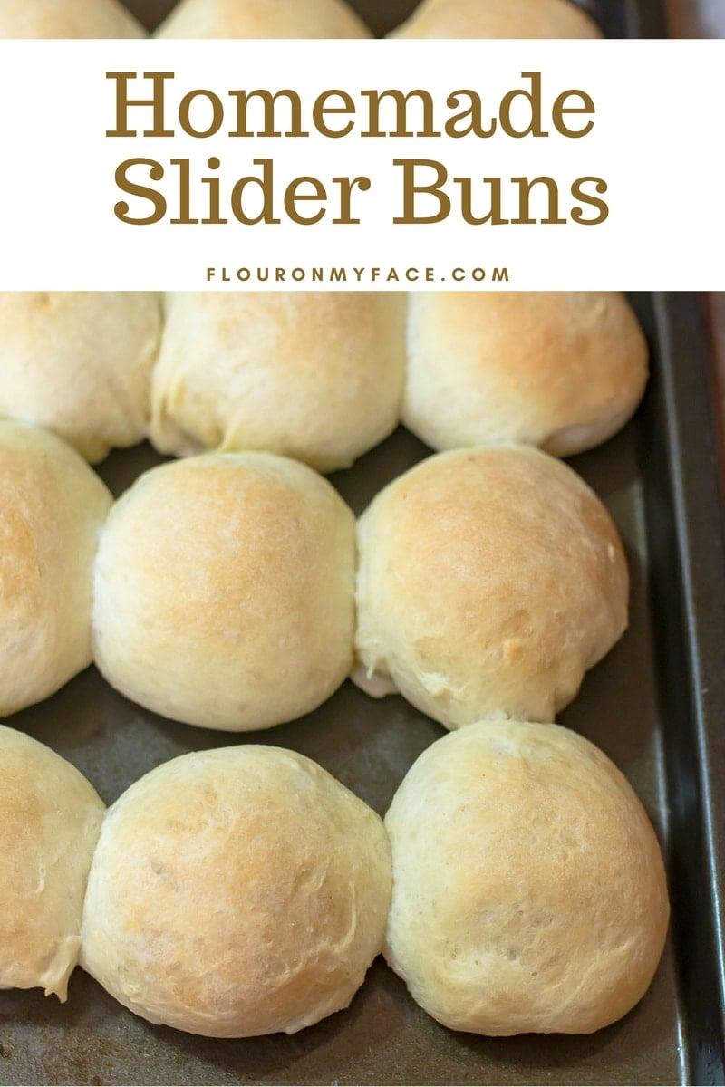 Freshly baked homemade slider buns on a cookie sheet.