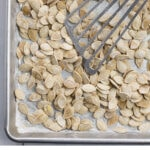 Salted and roasted pumpkin seeds on a baking tray with a metal spatula as they cool.