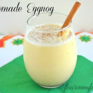 A glass of homemade eggnog on a holiday table.