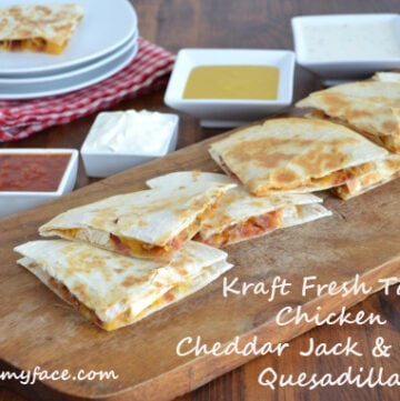 Chicken Cheddar Jack & Bacon Quesadillas served with dipping sauces on a wooden serving board.