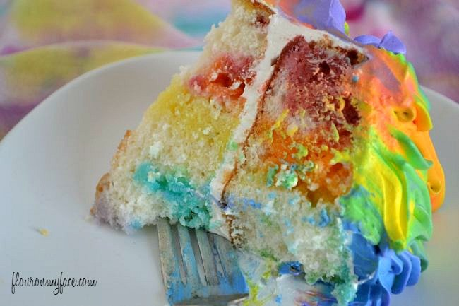 A colorful slice of Rainbow Jello Poke Cake via flouronmyface.com