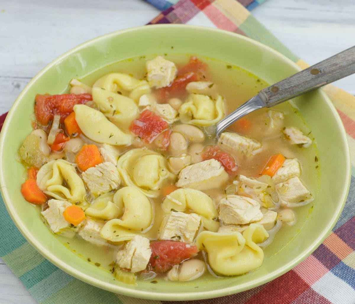 A bowl of tortellini soup with chicken.