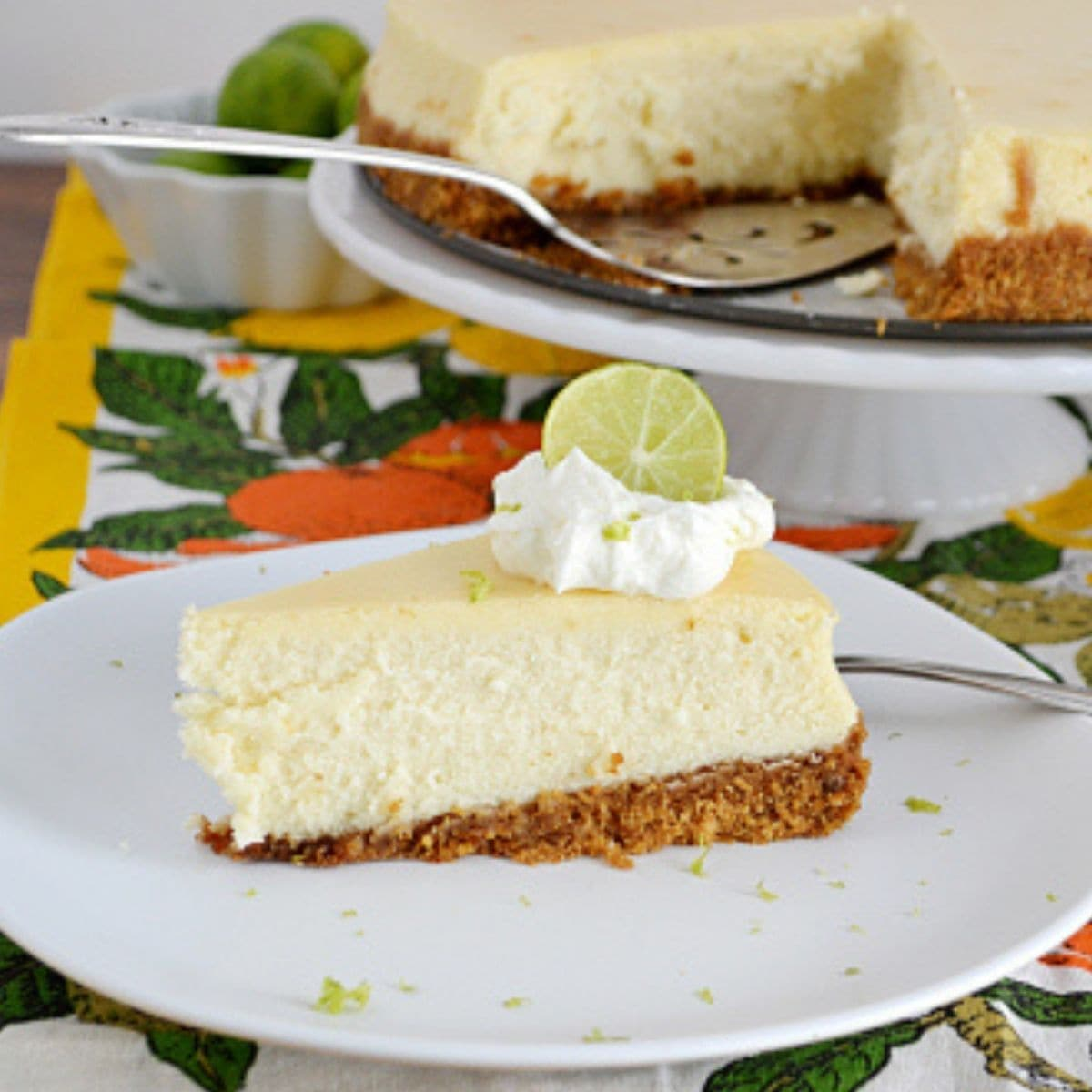 Slice of Key Lime Cheesecake garnished with whipped cream and lime wedge.