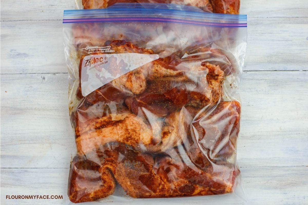 Seasoned boneless country style ribs in a plastic bag.