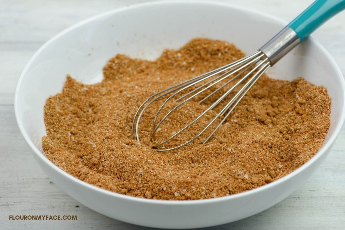 Mixing rub spices together in a bowl with a whisk.
