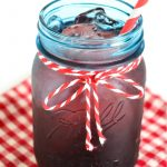 Blue vintage mason jar filled with homemade black cherry soda
