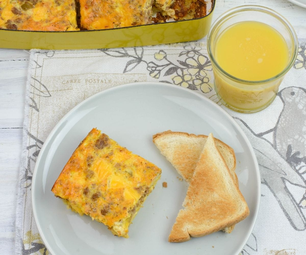 Cheesy Egg Sausage Breakfast Casserole served with toast and orange juice.