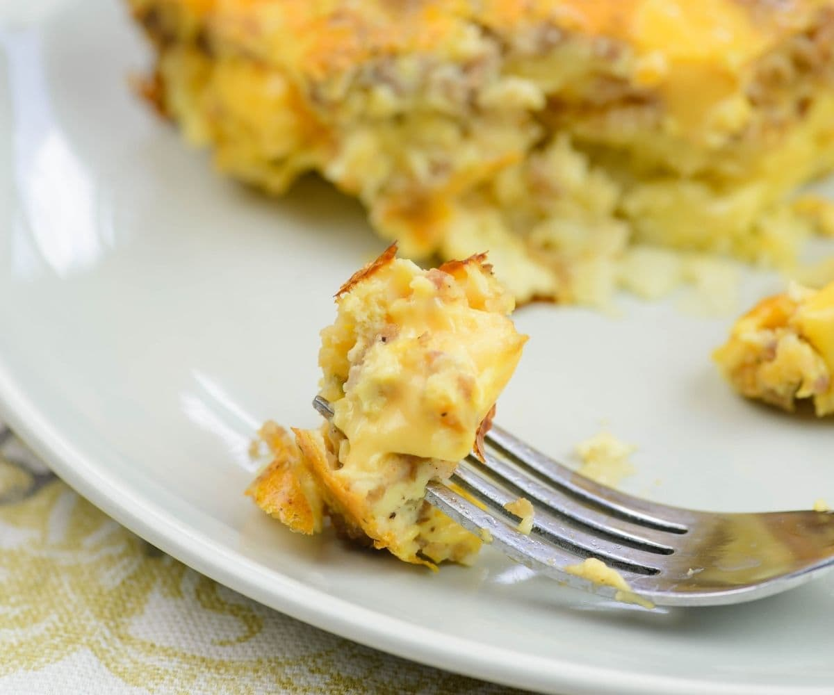 A forkful of cheesy Velveeta Breakfast casserole resting on a plate.