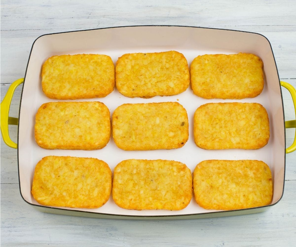 Baked hash brown patties arranged in a single layer in a casserole pan.