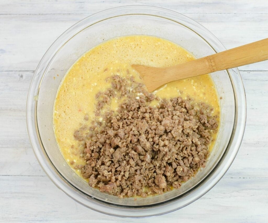 Adding browned breakfast sausage to a bowl of beaten eggs.