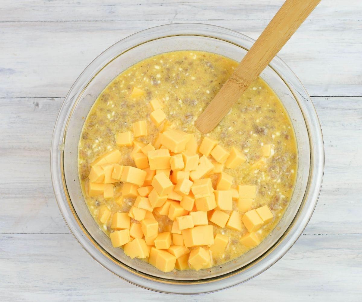 Adding cubed Velveeta cheese into egg mixture.