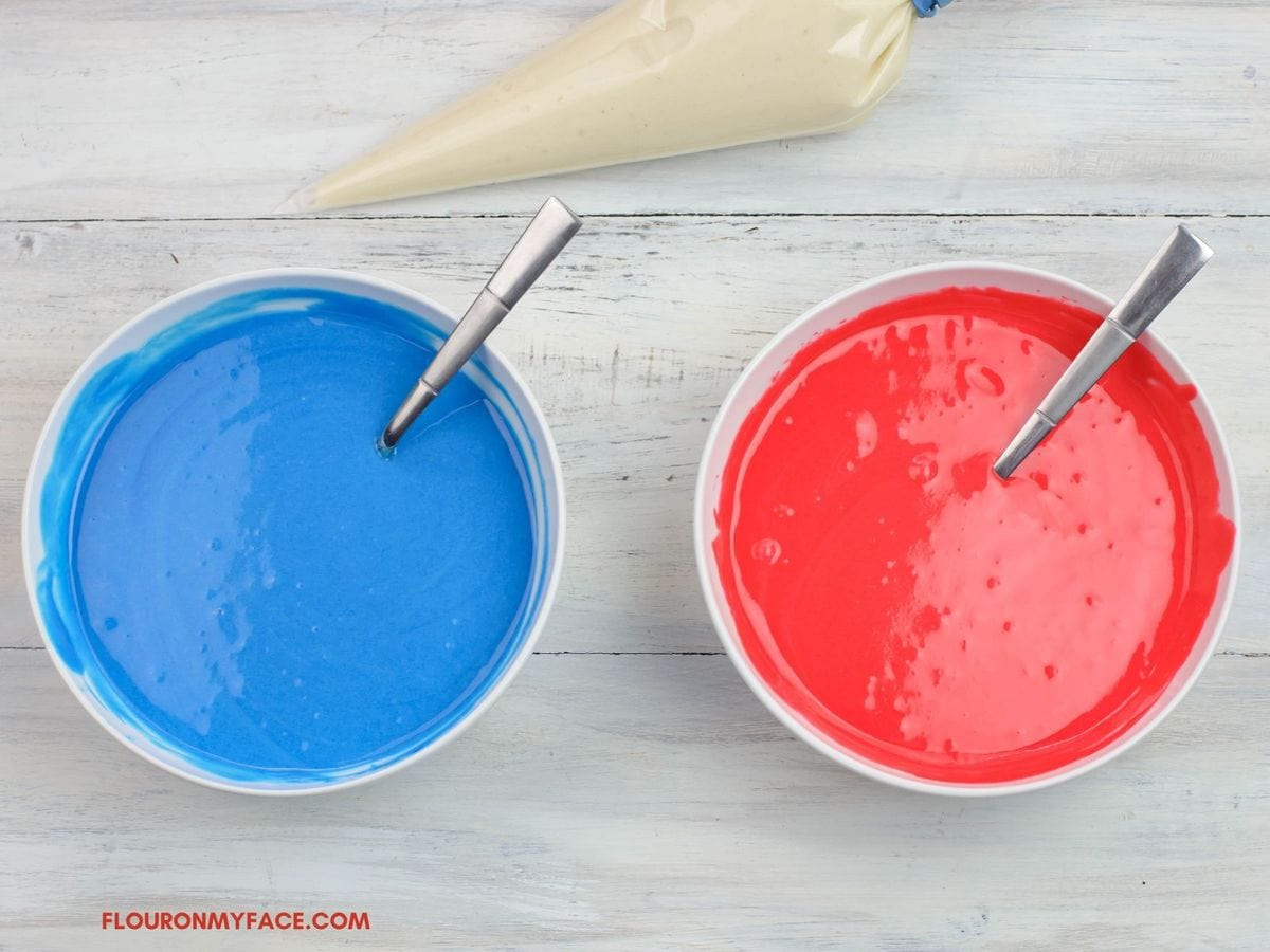 2 bowl of white cake batter that has been colored red and blue.