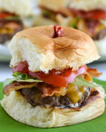 Closeup of a stuffed cheeseburger slider with bacon, tomato and lettuce.