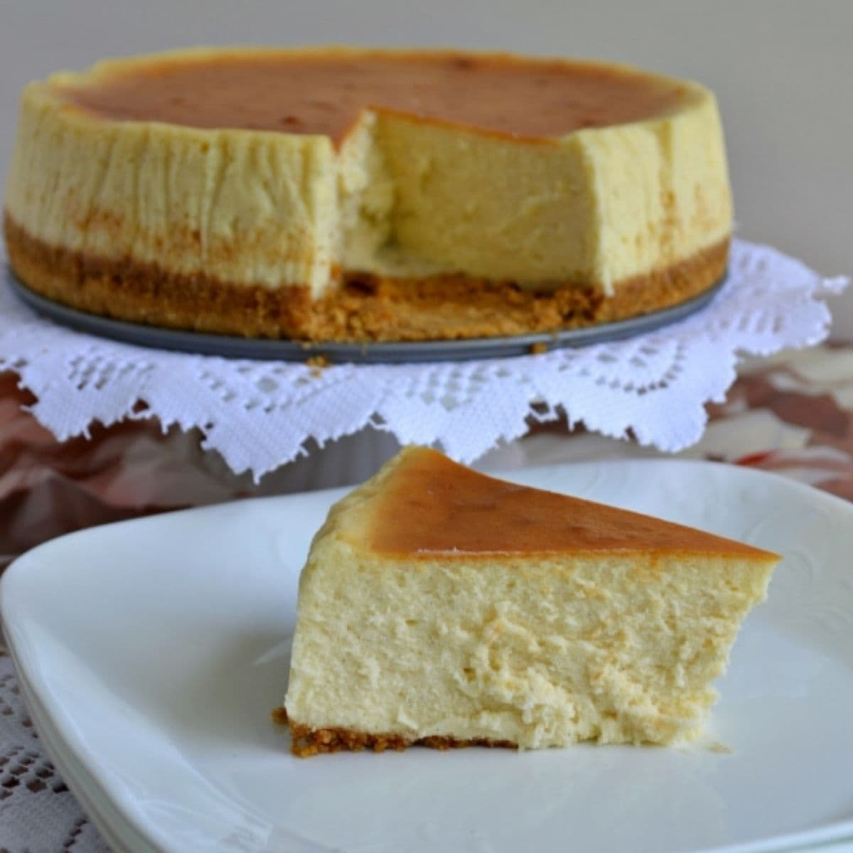 A slice of Vanilla Bean Cheesecake on a plate with the cheesecake in the background.
