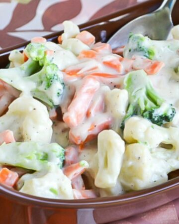 broccoli florets, cauliflower and carrots covered in a rich cream sauce in a serving tray.