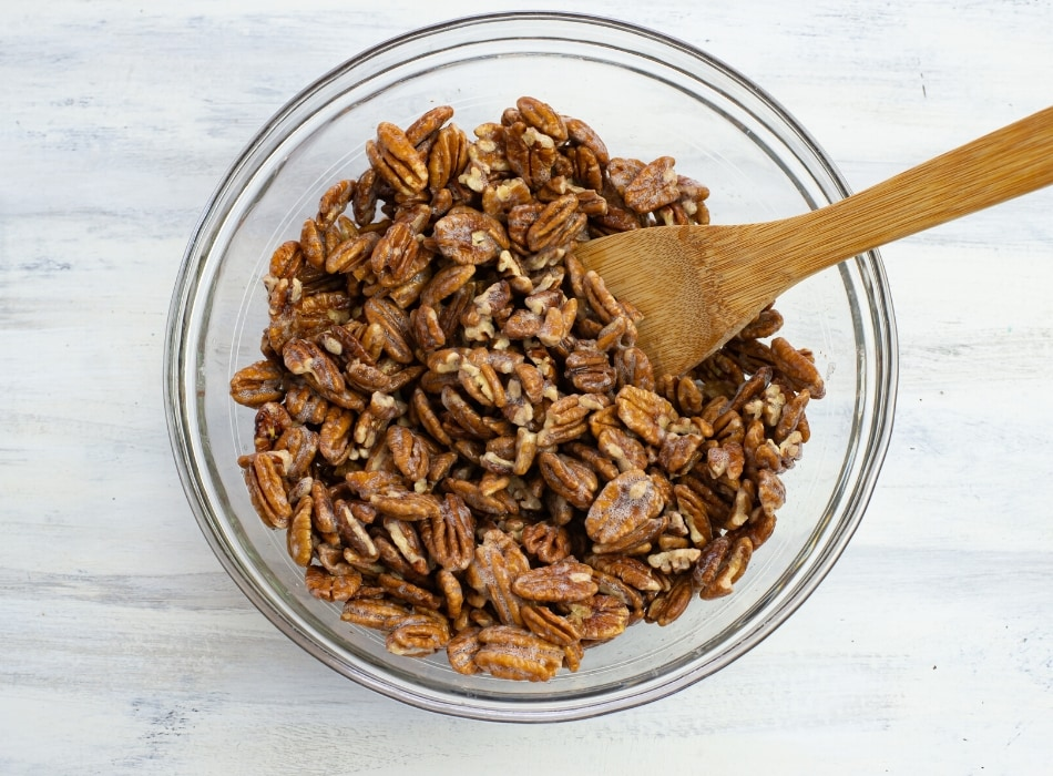 A bowl filled with pecan halfs that have been tossed with egg whites for Candied Pecans