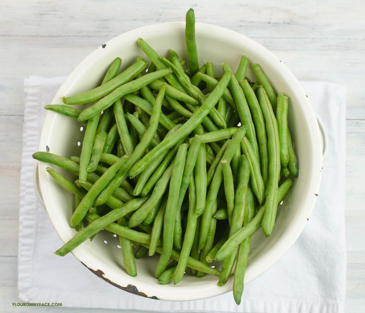 Fresh green beans in a white metal collander.