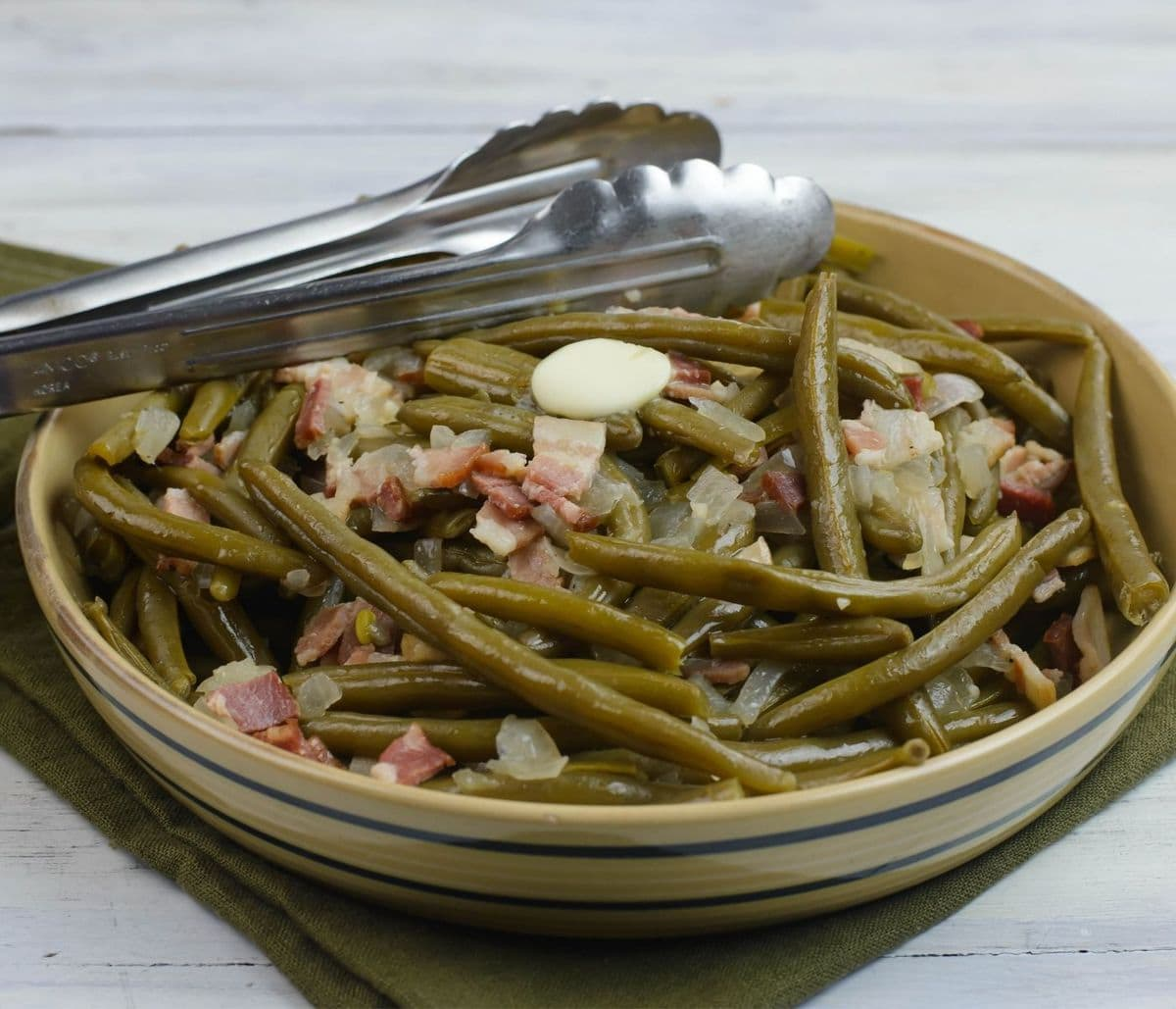 Serving bowl of green beans with bacon with a pair of tongs on the edge of the bowl.