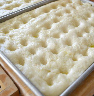 Sourdough focaccia dough rising in a baking pan.