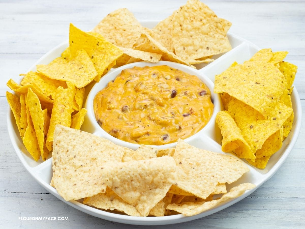 Chili Cheese dip served with corn and flour chips in a serving dish.