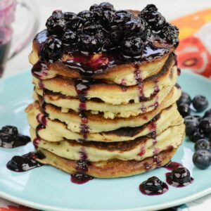A tall stack of homemade buttermilk pancakes covered in blueberry syrup on a plate.