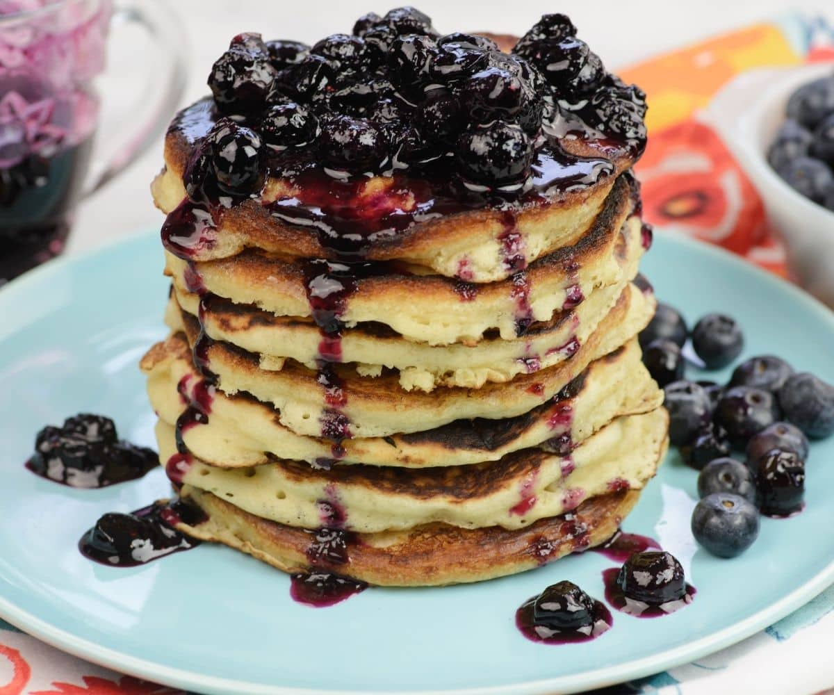 A stack of fluffy buttermilk pancake drizzled in blueberry pancake syrup.